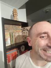 Photograph of John Elliott in front of Mad Magazine books.