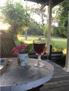 Photograph from an outside undercover place with a table, flowers and a glass of red wine looking out to a green lawn with some eucalyptus tress.