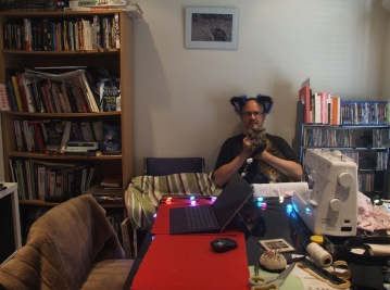 Wade Bowmer wearing bear ears holding his cat sitting in his lounge room with a couch, sewing machine, bookcases, computer screen and colourful lights