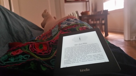 Ainslie's repose feet with kindle in her lap