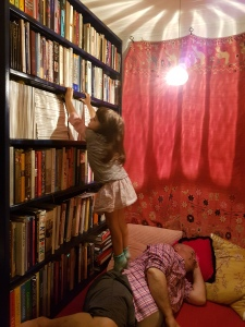4 year old standing on her sleeping father reaching for a book in her family's books nook