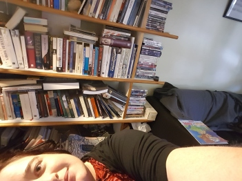 Fifiramous lying on her side with her bookcase in the backgroup piled horizontally and vertically