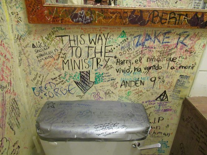 Toilet stall covered with grafitti