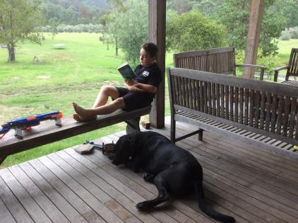 Nephew and his big black dog on his verandah reading his book while overlooking a lush, green farm.