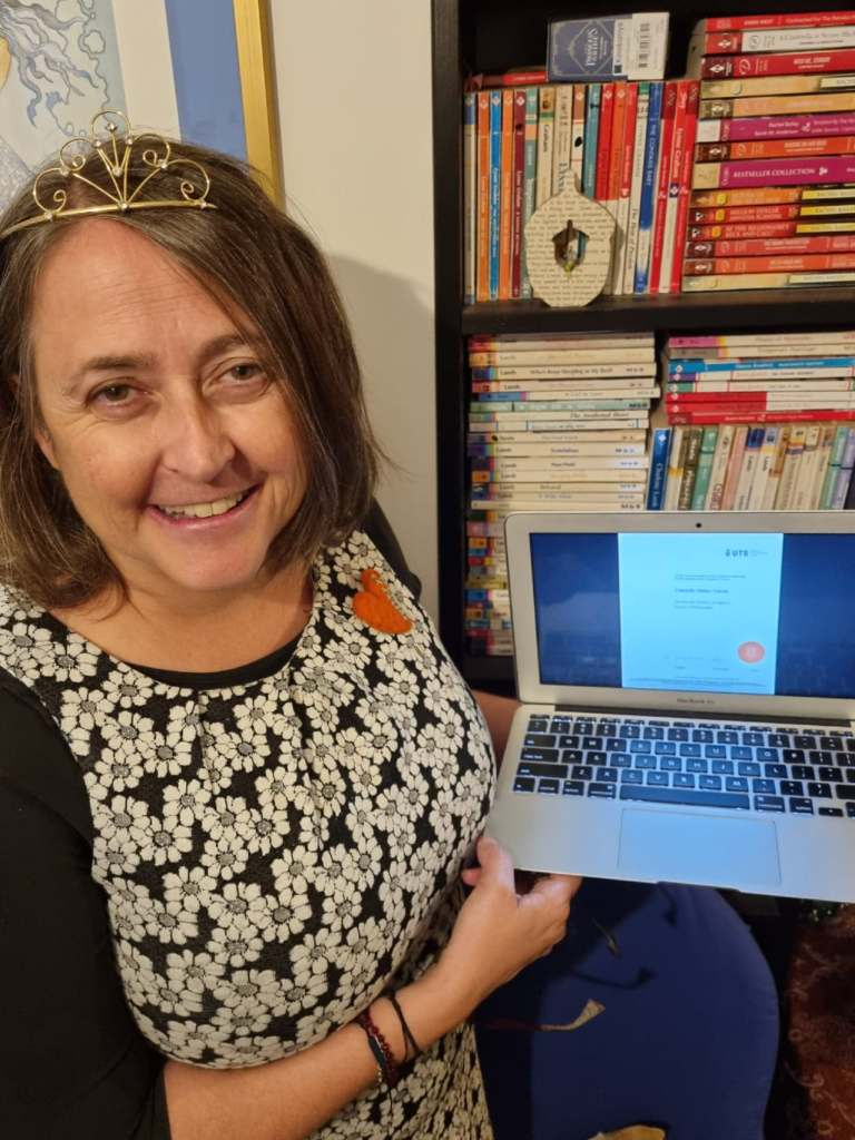 A photograph of me wearing a tiara, a black and white dress with daisies and a felt heart brooch. I am holding my laptop computer with an image of my esteemed PhD blurring the screen. Behind me is a bookcase filled with category romance fiction.
