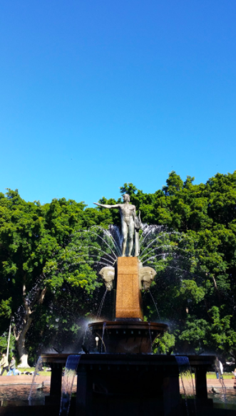 Archibald Fountain is a water fountain in Sudney. The focus is on a young Apollo with green trees as a backdrop with a bright blue sky.